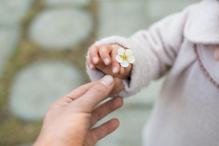 Contrôle de la motricité fine - enfant tenant une fleur en pince - Blog d'activités pour enfants