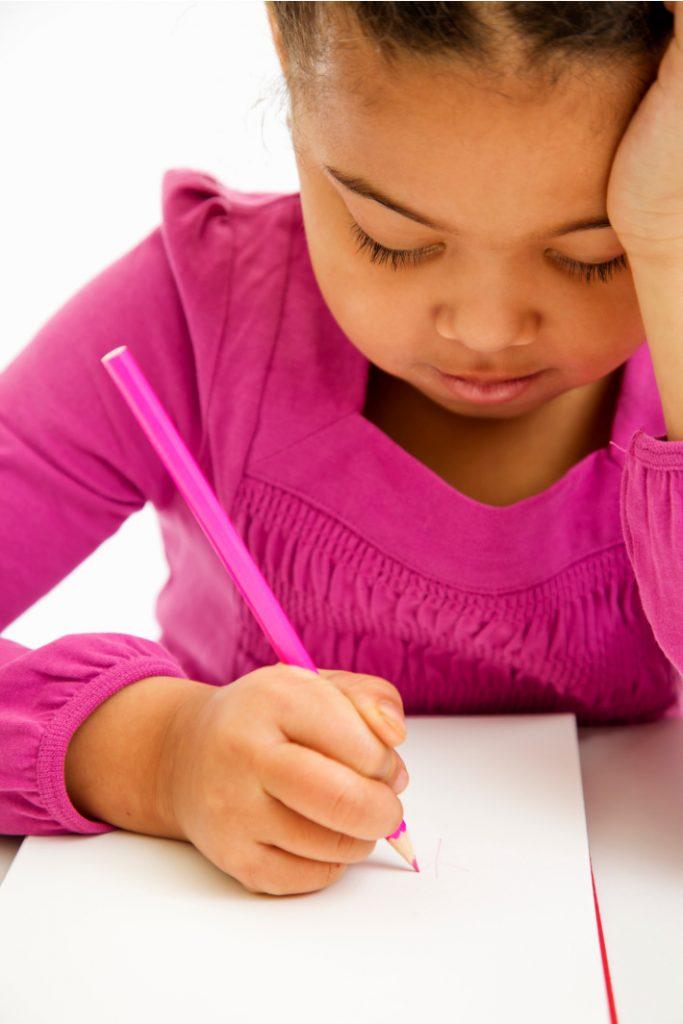 L'outil d'écriture aide les enfants à apprendre à tenir leur crayon correctement - Blog d'activités pour enfants - petite fille écrivant sur du papier avec une mauvaise prise de crayon