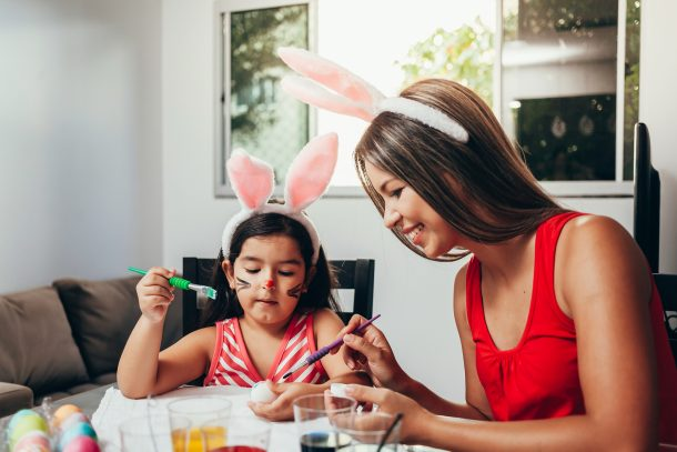 A mom and daughter with bunny ears painting Easter Egg decorations on boiled eggs.
