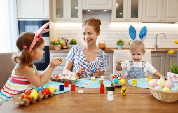 A family using various Easter egg designs to paint eggs wearing bunny ears.