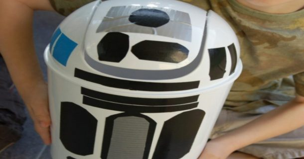 R2D2 trash can made out of a white trash can, with black, silver, and blue tape making R2D2's features
