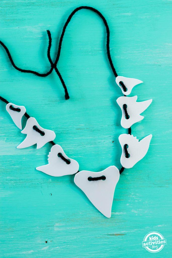 a shark teeth necklace on a blue table