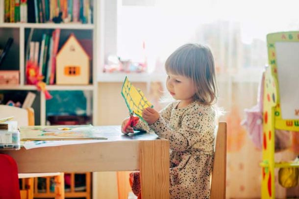 A preschool girl is cutting up a piece of yellow paper with her scissors while sitting at a small table in her room.