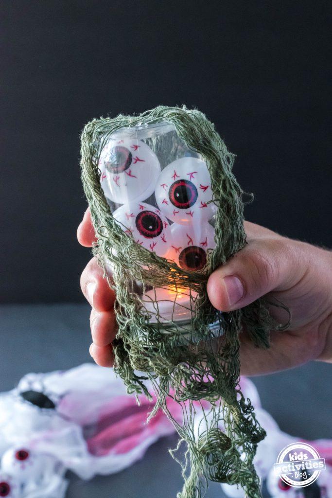 Plastic eyeballs lantern with led lights covered in green netting.