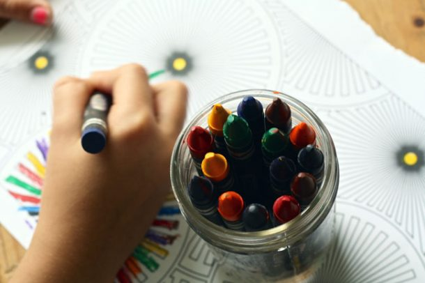 A young boy is coloring a coloring sheet with crayons. Next to him is a glass jar filled with crayons.