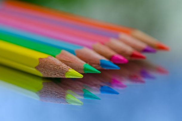 A row of eight colored pencils freshly sharpened and sitting on a glass surface so their reflection is visible.