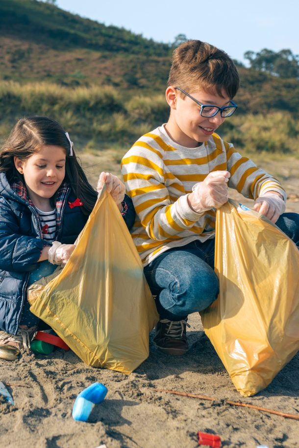 Children volunteers picking up trash on the beach