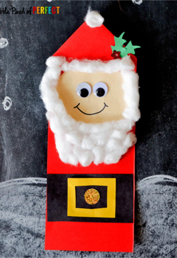 Christmas Santa crafts for kids with a paper santa with a red suit, black belt and white cotton beard.