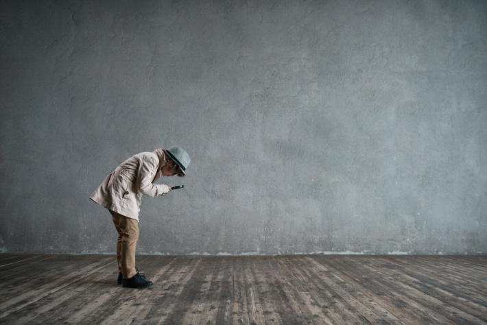 Decoding the message of a secret code - Kids Activities Blog - boy with magnifying glass searching an empty room