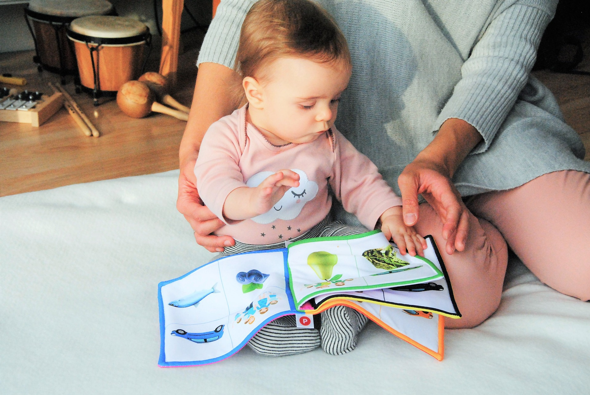 Mother with baby and a book with animals and no words