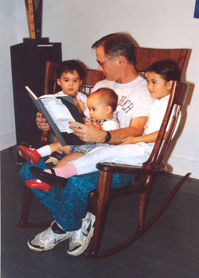 photo of family sitting and reading in a rocking chair designed for story time