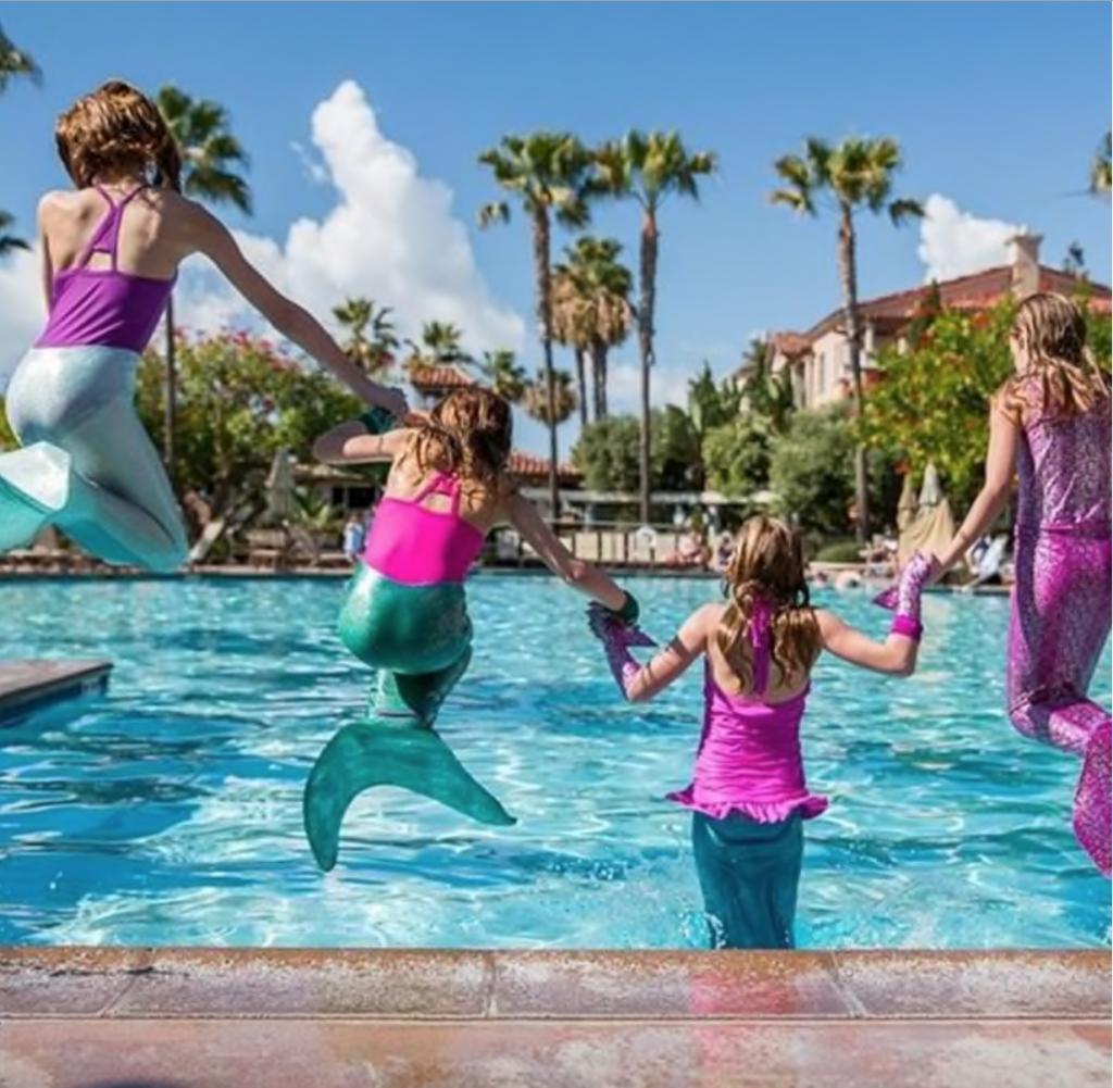 4 niños saltando a la piscina con colas de sirena de tela para niños
