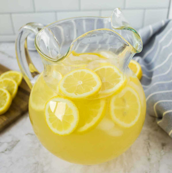 A jug of fresh homemade lemonade made from lemon juice, water and sugar topped with lemon slices and ice cubes ready to drink.