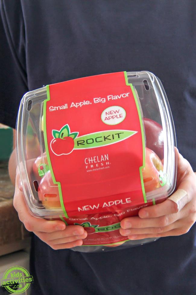 garçon tenant un récipient en plastique de mini pommes rockit