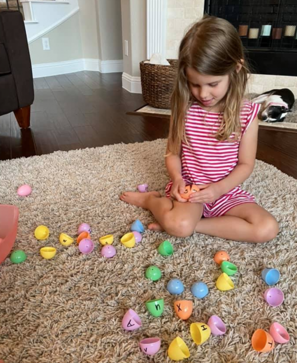 Easter egg plastic egg letter matching game for preschoolers - girl trying to match two sides of a plastic egg