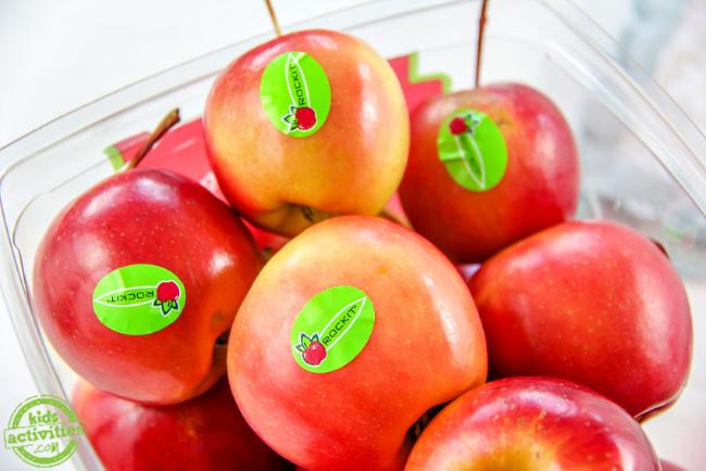 un récipient plein de pommes rockit rouges et jaunes