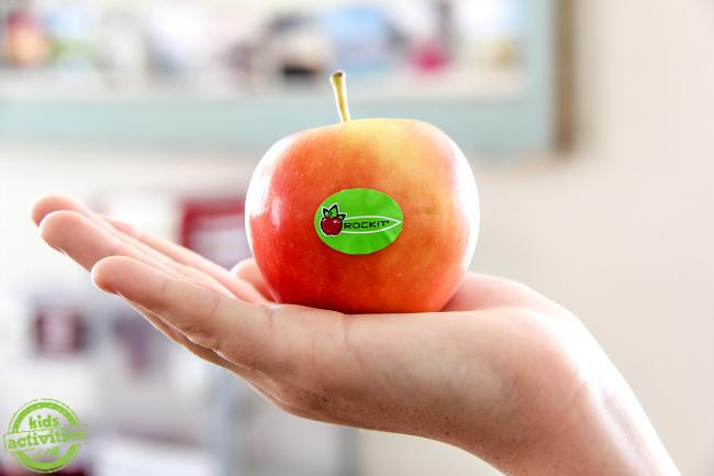 une main d'enfant tenant une mini pomme rouge
