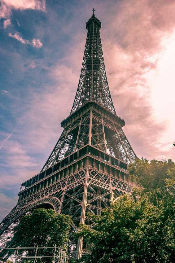 The tall Eiffel Tower in Paris, France; photo is taken from the ground looking up a the side of the tower.