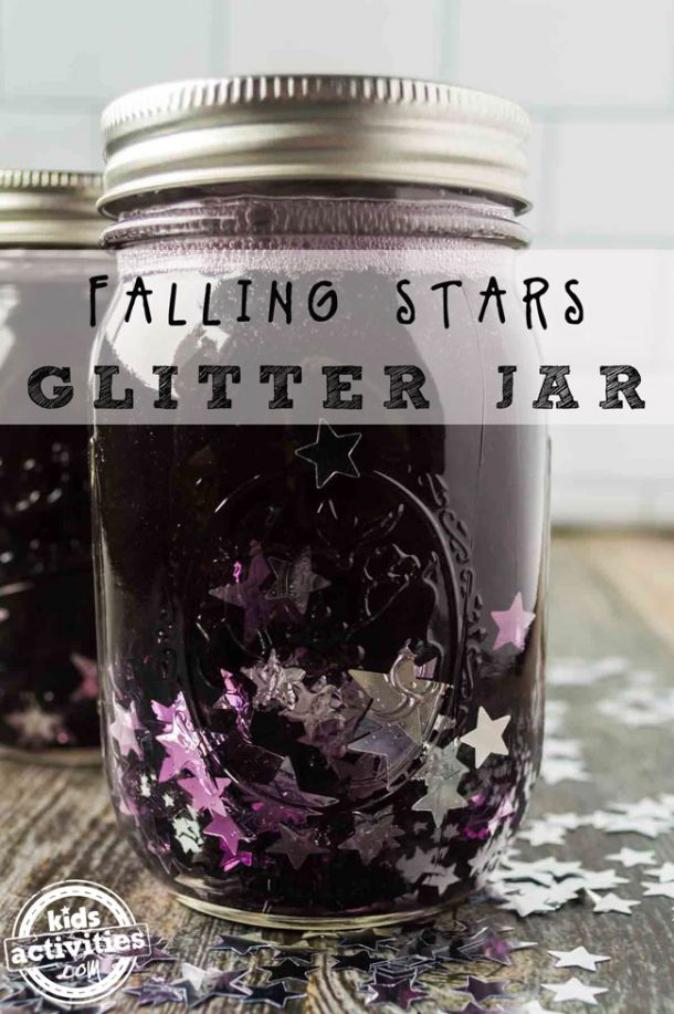 A mason jar filled with purple water, clear glue and silver confetti with a lid on top. There is a second identical jar in the background.