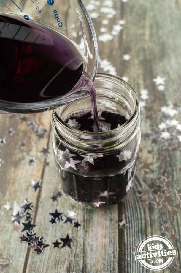 A mason jar filled with glue, purple water and silver star confetti. A person is pouring the purple water into the jar.