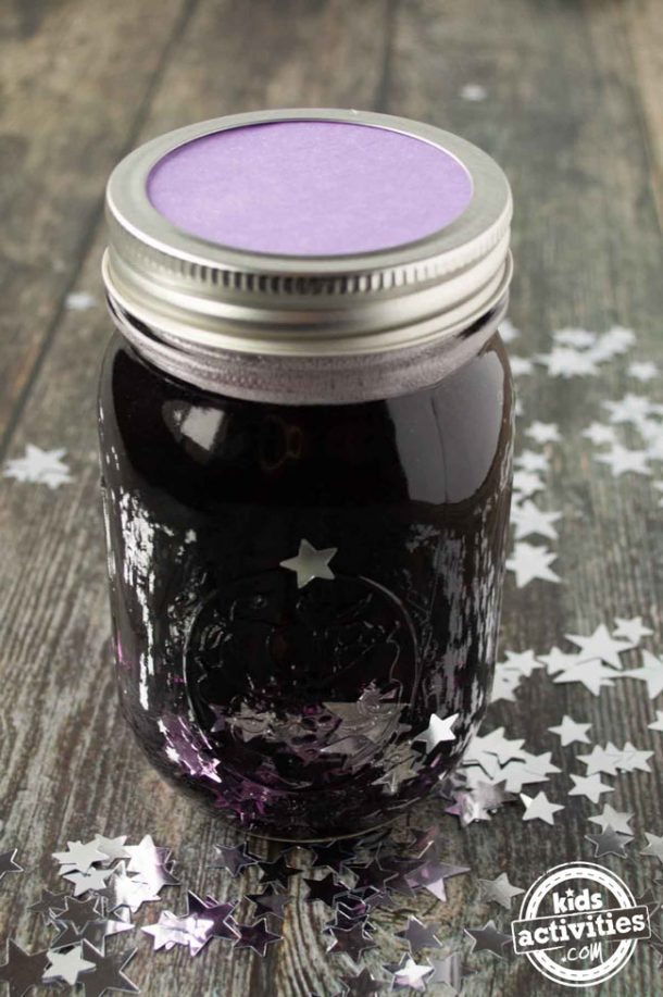 A mason jar filled with glue, purple water, and silver confetti with the top on. You can see purple construction paper under the lid.