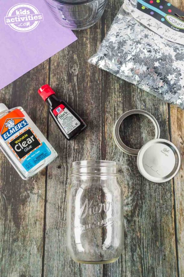 Everything you need to make a falling stars glitter jar, including the Mason jar, lid, clear glue, black dye, purple construction paper and silver star confetti.