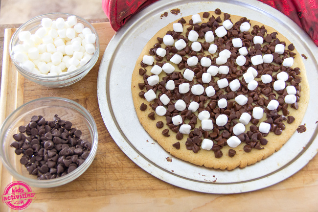 a giant cookie covered in chocolate chips and mini marshmallows