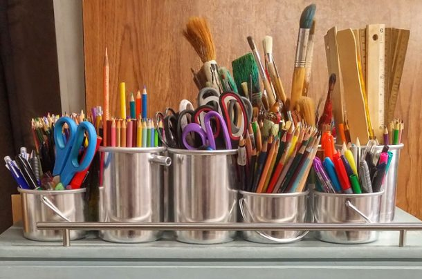 stainless steel containers filled with colored pencils and scissors and paintbrushes and rulers and many other school supplies.