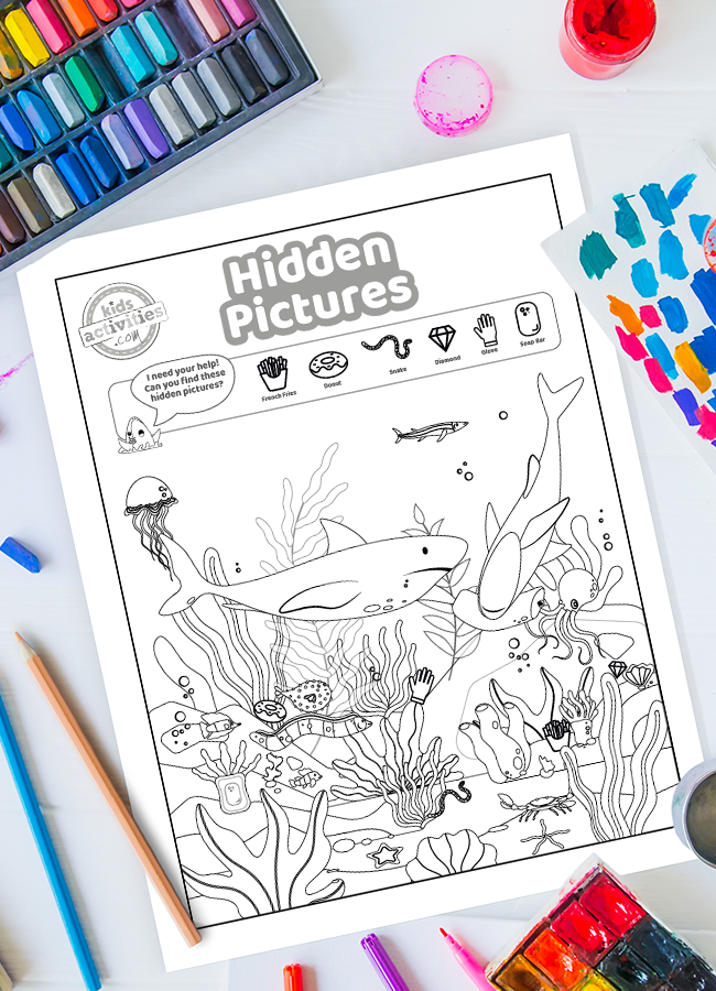 Puzzles for Kids - Hidden Pictures Shark Worksheet surrounded by paint, crayons and other art supplies