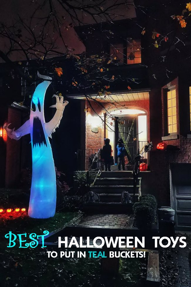 On Halloween night, it is the outside of a house decorated with Halloween decor and two costumed children are at the door trick-or-treating with their pumpkin buckets.