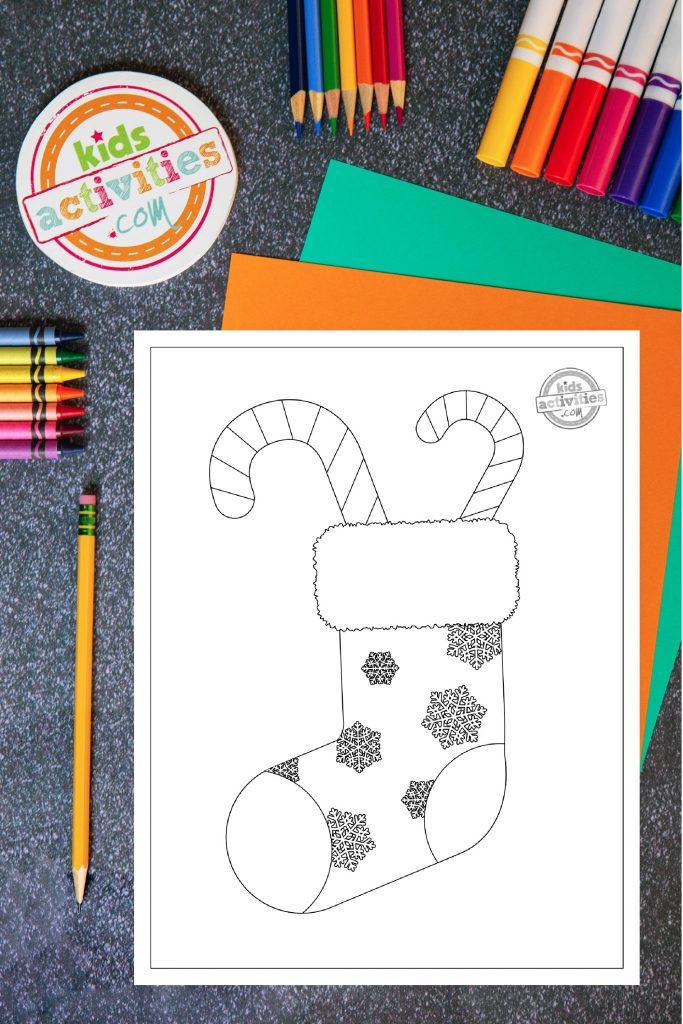 Imprimez et coloriez ce coloriage de Noël en sucre d'orge !  Coloriage d'un bas de Noël décoré de flocons de neige sur un bureau entouré de crayons, de marqueurs et de crayons de couleur aux couleurs vives.