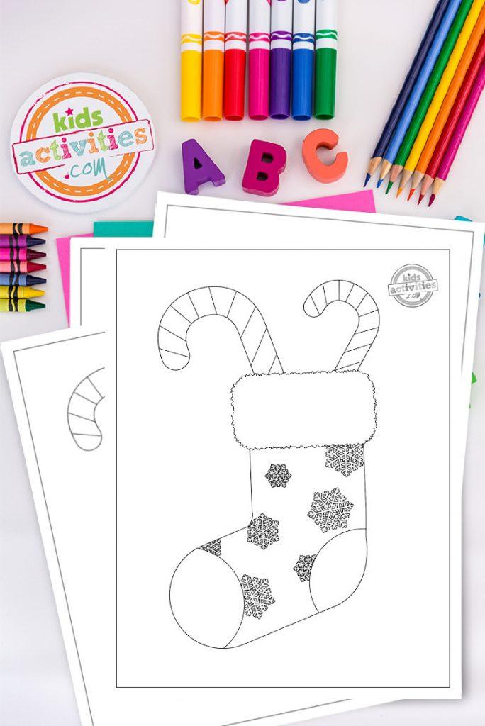 Imprimez et coloriez ce coloriage de Noël en sucre d'orge !  Ce doux imprimable est amusant, festif et mettra vos enfants dans l'esprit des vacances.  Coloriage d'un bas de Noël recouvert de flocons de neige avec des cannes de bonbon sur un bureau blanc entouré de fournitures d'art et d'artisanat colorées.
