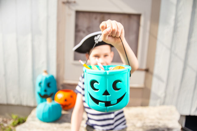 A boy wearing a pirate hat and a striped shirt holds up a teal bucket filled with pencils and toys and other non-food items. He is standing in front of a house with two more teal pumpkins and an orange pumpkin.