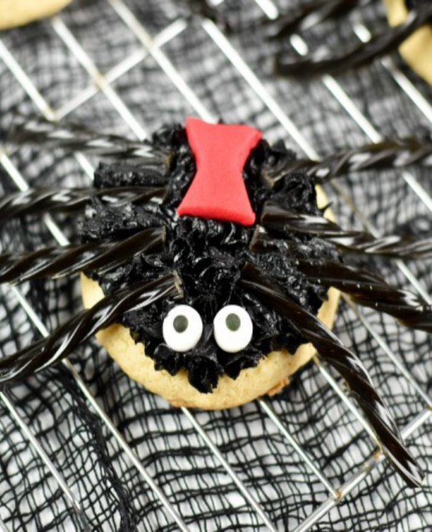 spider cookies made from a sugar cookie, with white sugar eyes, black frosting, red fondant to look like a black widow hour glass and black licorice legs