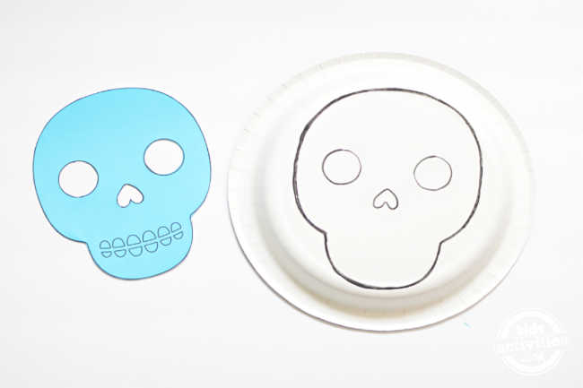 skull template traced on a back of the paper plate for making maks for dia de los muertos
