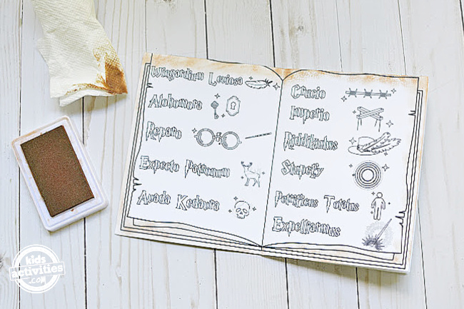 list of harry potter spells page is open with a stamp pad and paper towel on the side to teach on how to give distress look
