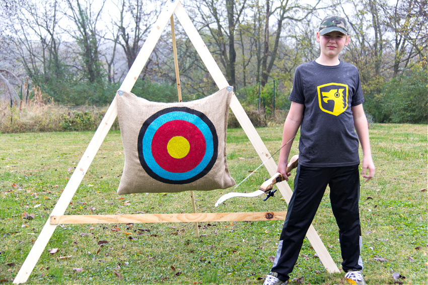 a boy standing next to a homemade archery stand