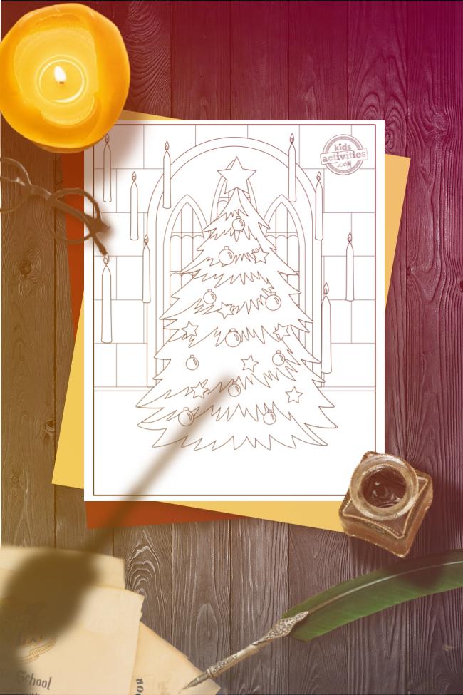 Coloriage de Poudlard d'un arbre de Noël à l'intérieur de Poudlard encadré par un arc en briques et entouré de bougies flottantes, avec la page à colorier montrée sur un bureau en bois éclipsé par une baguette tenue au-dessus.