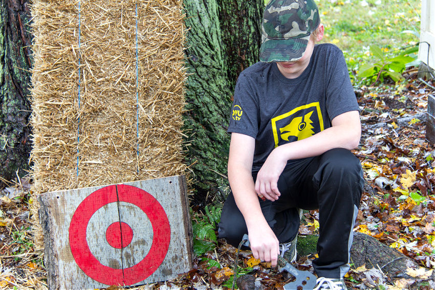 a boy holding an axe next to a handmade wood target