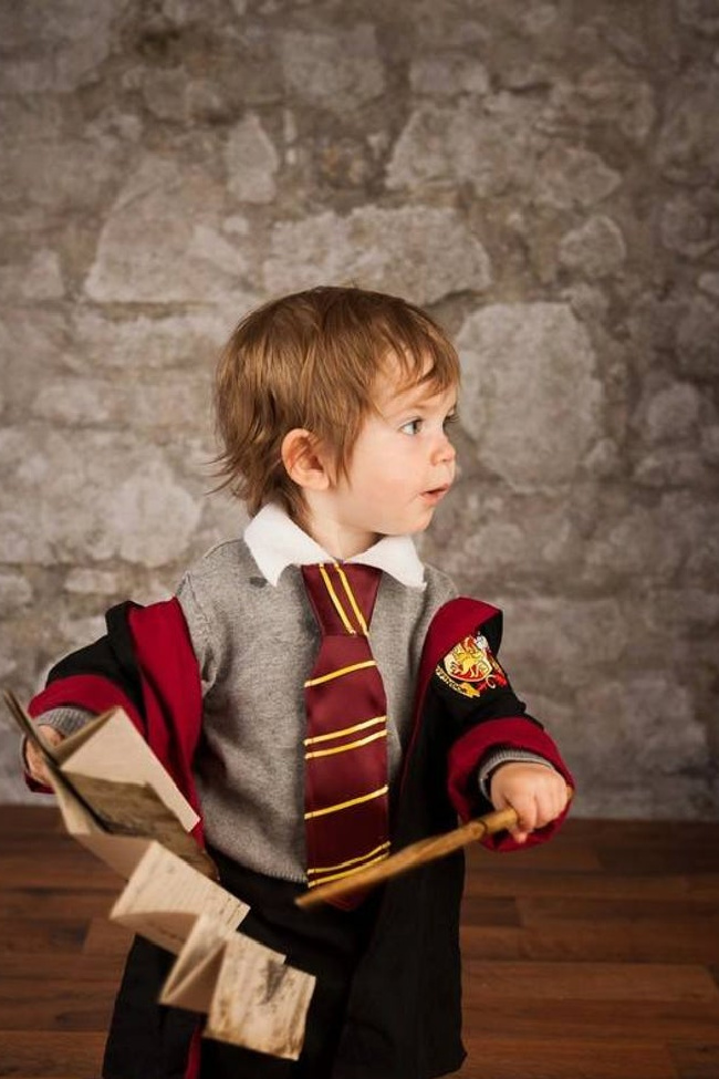 Harry Potter toddler costume on a little boy holding a wand and the Maurader's map in front of a stone wall.