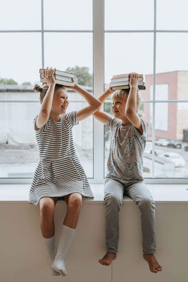 Two children who are holding stacks of books on their heads and sitting in a window seat inside a building two or three stories up. Looking at each other and smiling.
