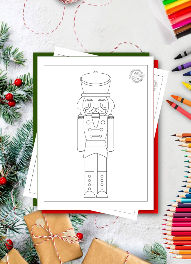Coloriage Casse-Noisette avec un grand soldat Casse-Noisette sur une surface blanche avec des cadeaux de Noël et des branches d'arbres de Noël, des crayons de couleur, des crayons et des marqueurs autour