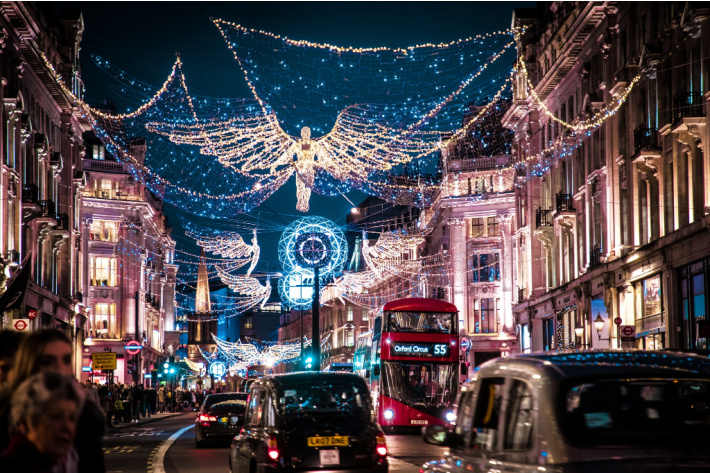 Christmas light town scene from London with holiday lights above street including an angel