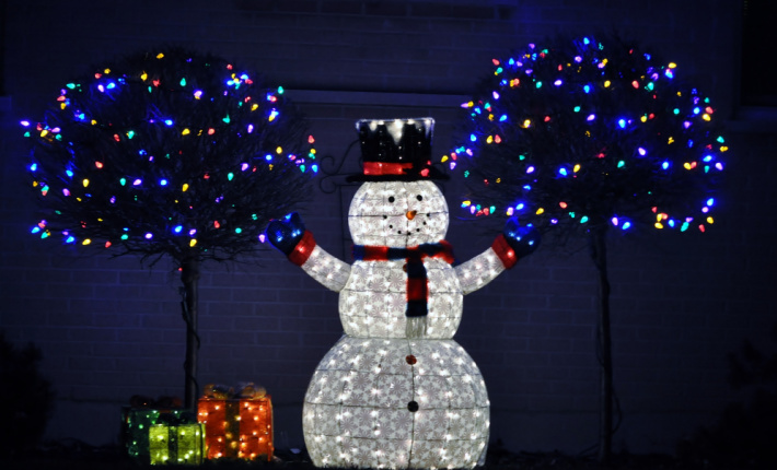 Lit snowman for the holidays with Christmas lights of many colors behind him found on light scavenger hunt printed from Kids activities blog