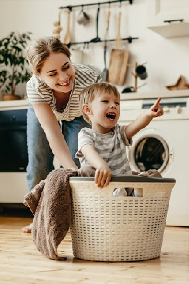 Mom is pushing her son in a laundry basket as they do chores together.