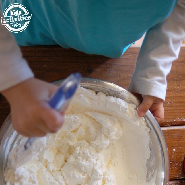 Étapes faciles de la recette de pâte à modeler comestible pour préparer la recette de pâte à modeler préférée des enfants - non toxique et ils peuvent avoir un goût - Kids Activities Blog - enfant mélangeant les ingrédients de la pâte à modeler ensemble