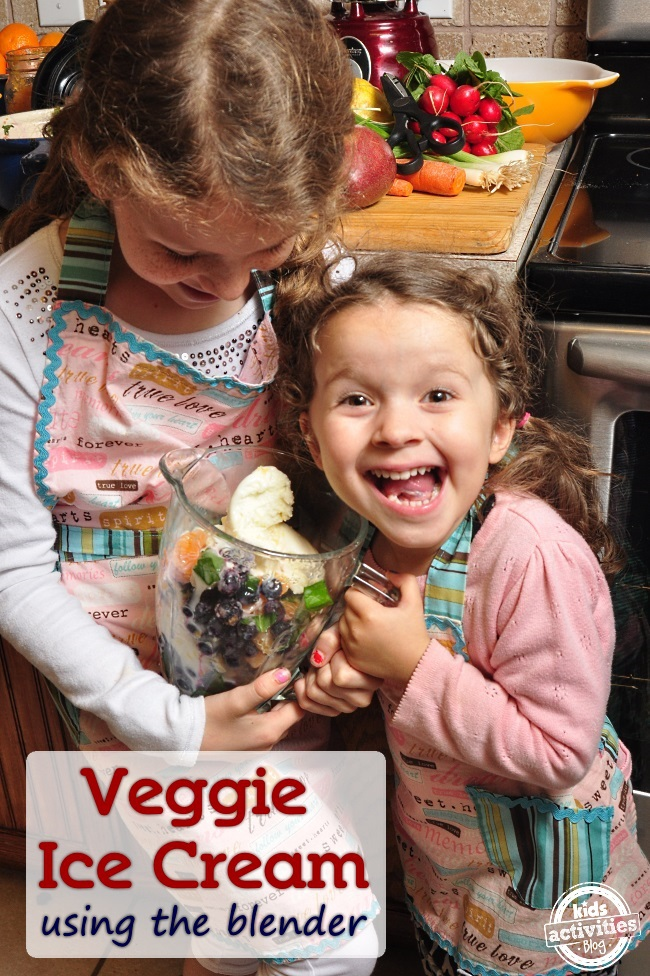 two girls making veggie ice cream in the blender - the blender has ice cream, oranges, spinach and blueberries in it.