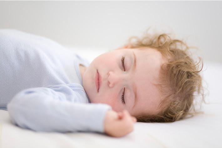 Obtenir 1 an pour dormir toute la nuit - bébé endormi avec un regard heureux sur le visage