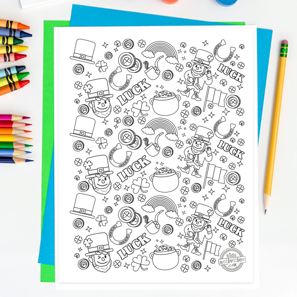 Coloring page of St Patrick's Day doodles with leprechaun, rainbow, shamrocks, gold coins, Ireland's flag on a desk with colored paper, pencils and crayons