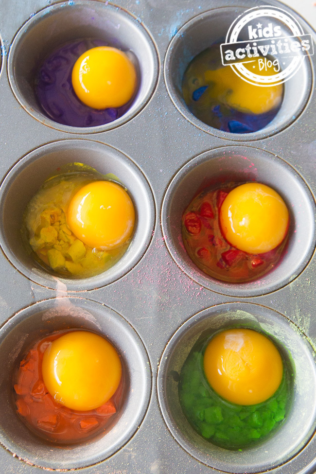 Egg yolk and chalk homemade paint recipe shown in progress of being made with egg yolks on top of brightly colored chalk in a muffin tin